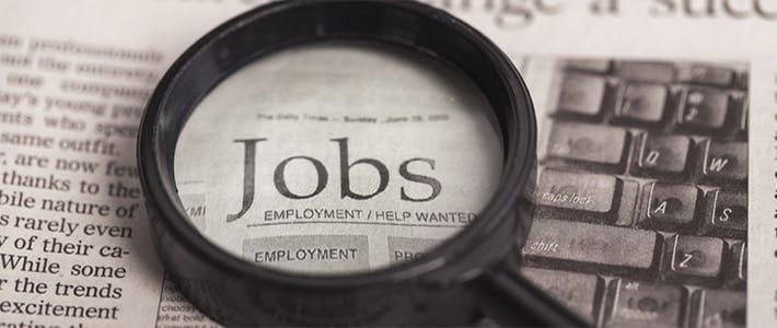 A newspaper with a magnifying glass focussing on the word 'jobs'