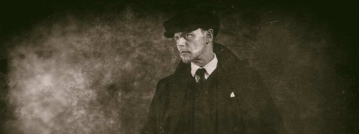 Peaky Blinders 1200x450 - Black and white photo of a man in a peaky cap