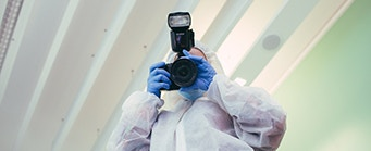 Social Sciences - About Us - Criminology Image 341x139 - Man in a crime scene suit with a camera