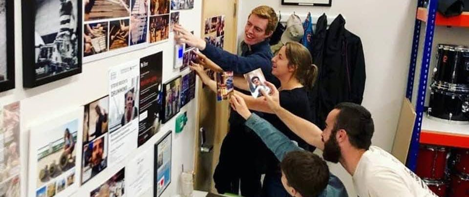 Adding to the photo collection in the percussion store - four people looking at photos on a wall