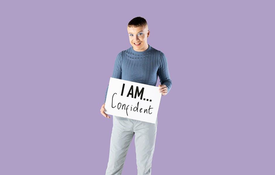 """学生亚历克斯·布莱克(Alex Black)举着一块写着""""我很自信""""的牌子"""