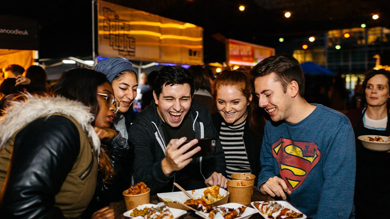 Picture of students watching funny video together on phone