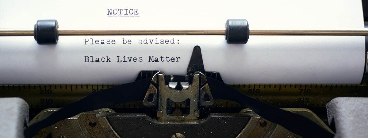 """BLM Books 1200x450 - Typewriter with the words """"Please be advised - Black Lives Matter"""""""