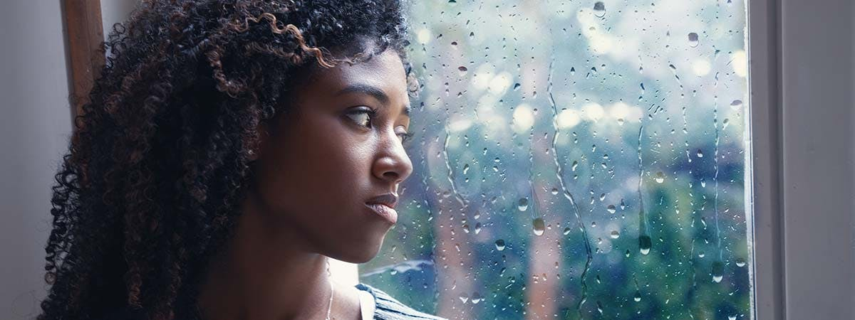 Blue Monday 1200x450 - Woman looking out of a rainy window