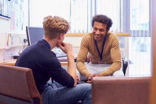 Two men sat opposite each other talking whilst sat down