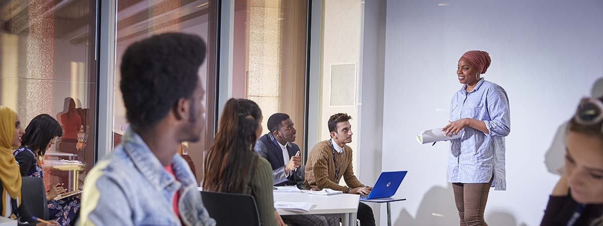 Business (Professional Practice) Course Image 1200x450 - People in a room with a woman giving a lecture