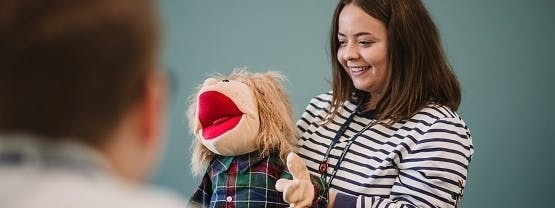 Student with toy puppet