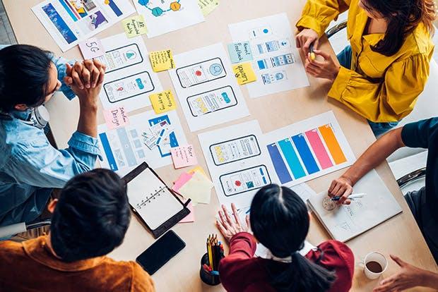 Creatives discuss their work around a table
