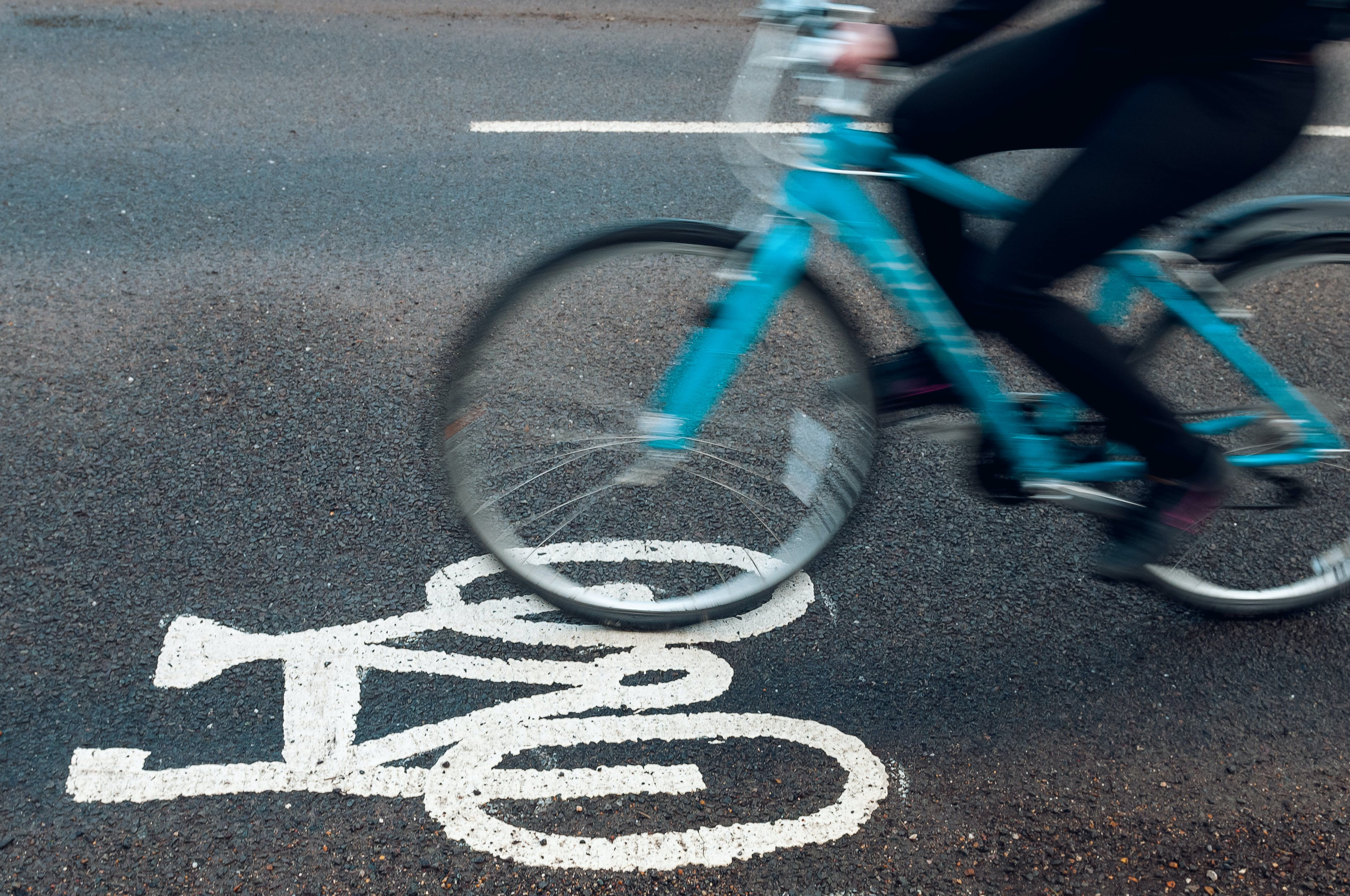 Someone riding a bike in a bike lane, with just the legs showing