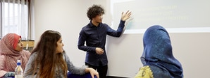 Economics - BA (Hons) Course Image 1200x450 - Men and women stood around a whiteboard