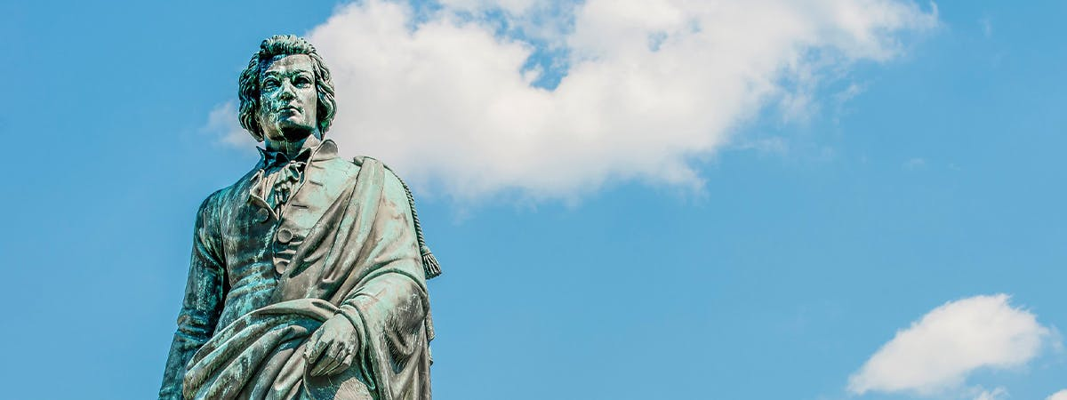 Bronze statue of a man with blue sky backround