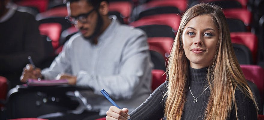 EVE CRM Top Image 880x400 - Woman sat in a lecture theatre, looking at the camera