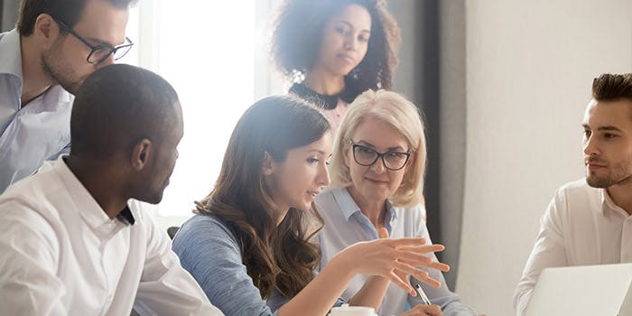 Executive Education 3 700x350 - People around a laptop