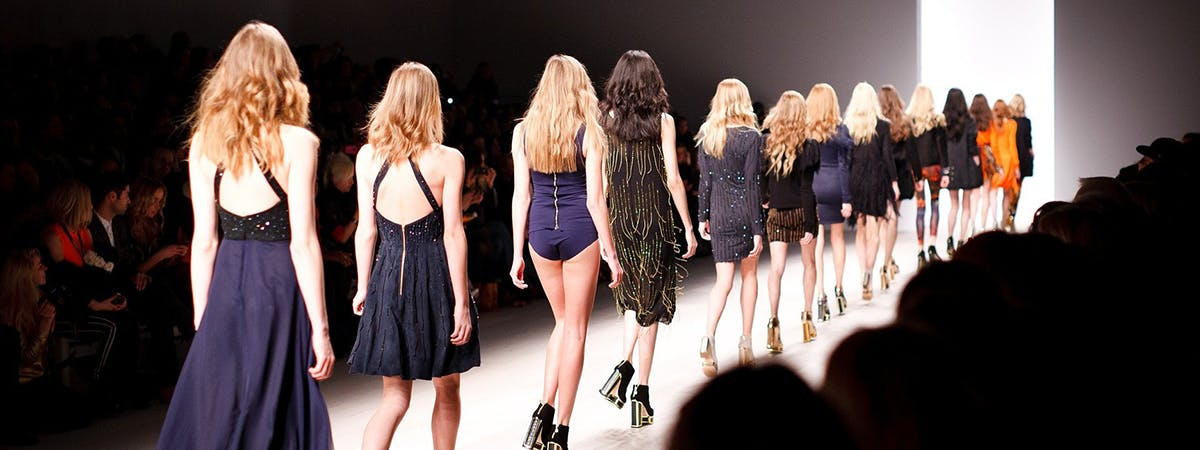 Models walking the catwalk in front of an audience