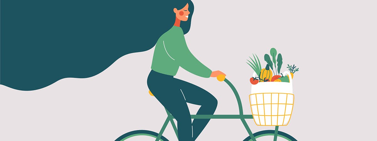 A woman rides a bicycle filled with sustainable produce, just one of the ways people can go green