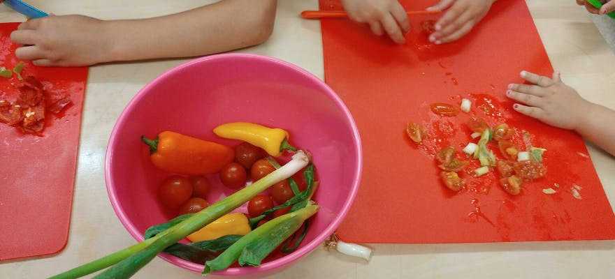 Young children cutting up vegetables