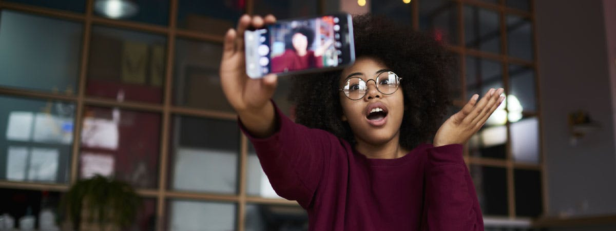 How to vlog your experience at university Image 1200x450 - Woman holding a phone, recording a video