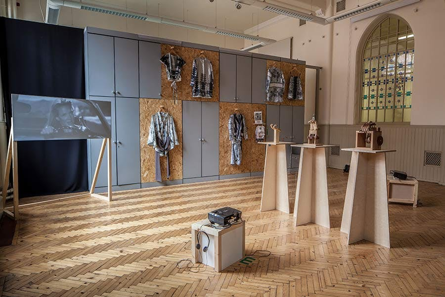 Margaret street studio with Fine Art work display, including video projected onto screen, 6 jackets hanging up on the wall at different levels and 3 wooden sculptures on stands