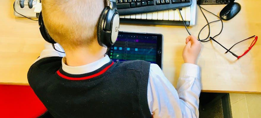 Student with headphone using an ipad to create music