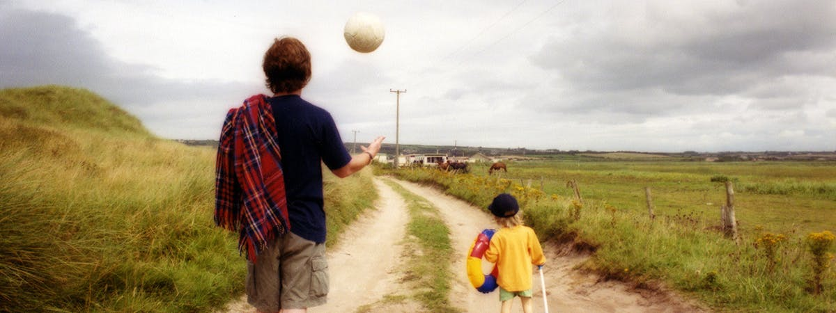 Photograph of man walking with son on a trail