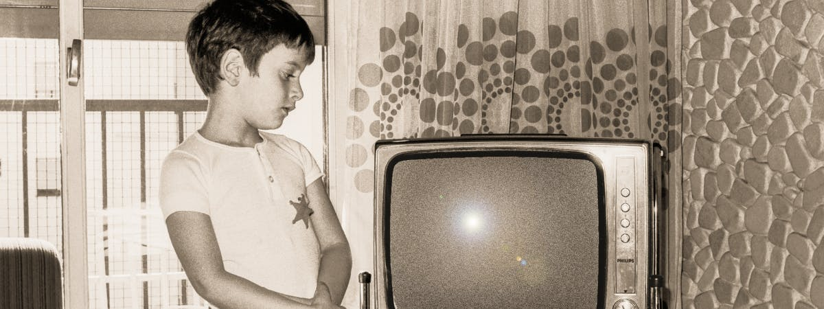 Young boy in the 60s looking at a TV