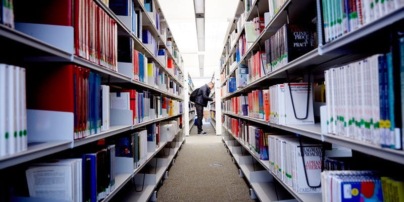 A man looking on shelves in library