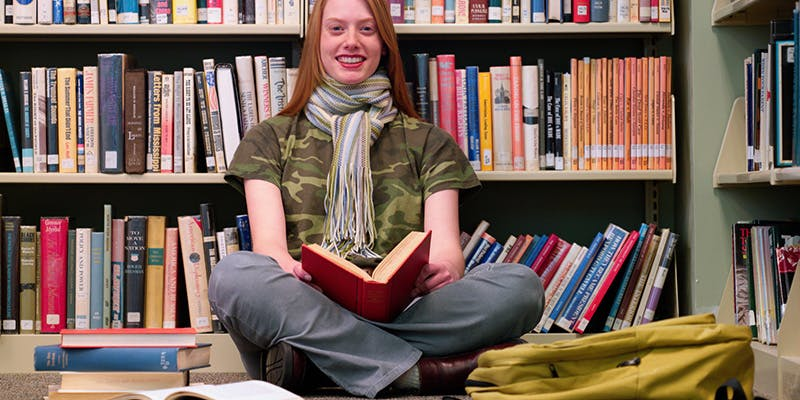A woman sitting and reading in the library