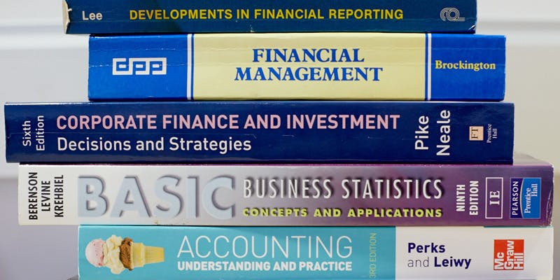 A neat pile of stacked Finance books