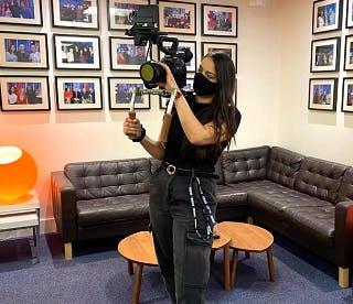 Liv Dias media graduate holding a TV camera