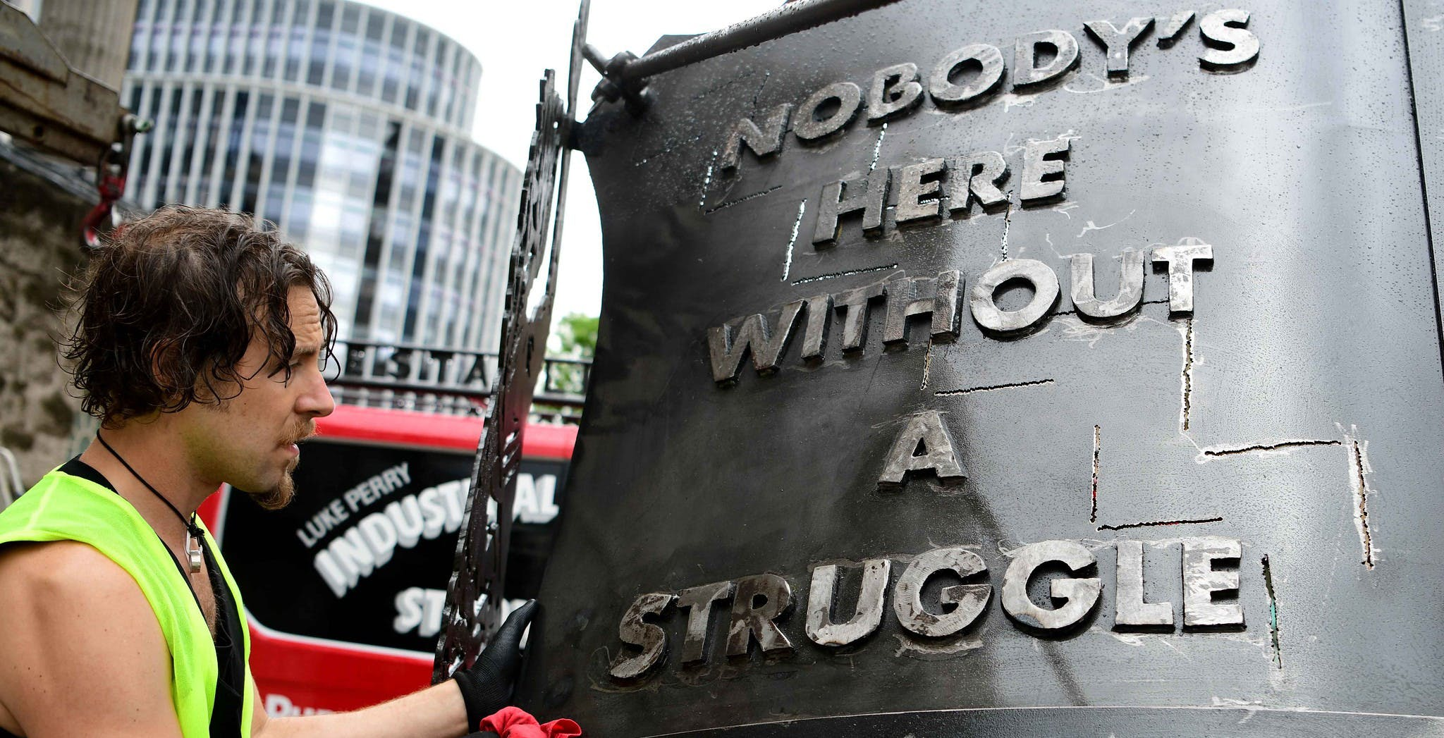 Image of artist Luke Perry in high-vis vest adding the final touches to his steel art crest which shows the words 'Nobody's here without a struggle'