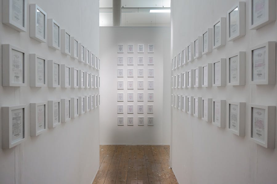 White wall corridor with lots of small white photo frames