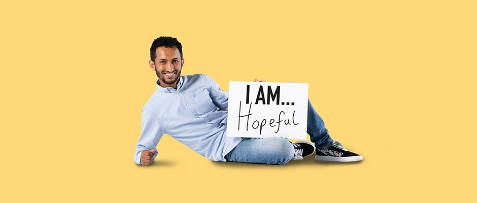 Student Malek Abdorab lying on the floor holding a sign that says 'I AM hopeful'