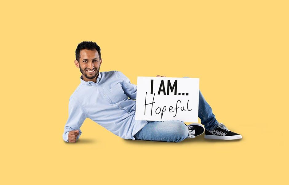 """学生Malek Abdorab躺在地板上,手里拿着一块牌子,上面写着""""我充满希望"""""""