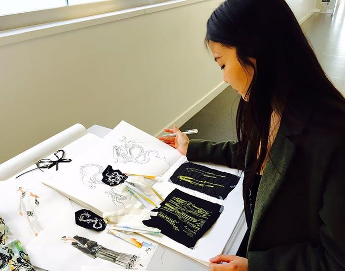 Mei-Sheng Sun working on her fashion designs