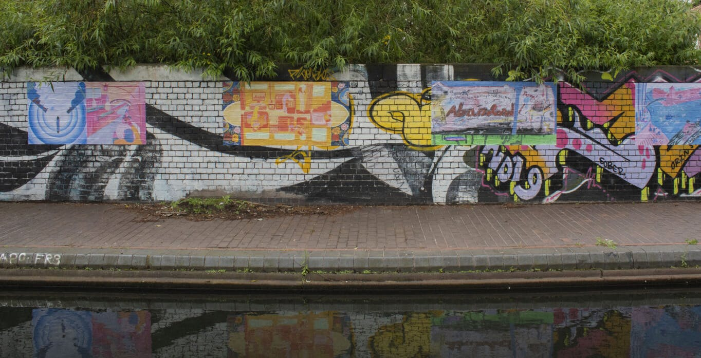 Image of colourful canalside artwork with foliage above