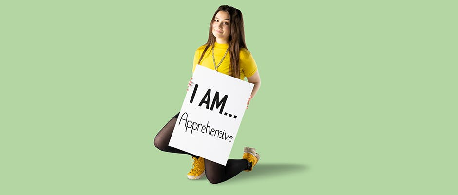 Student Natasha kneeling on the ground holding a board that reads 'I AM Apprehensive'.