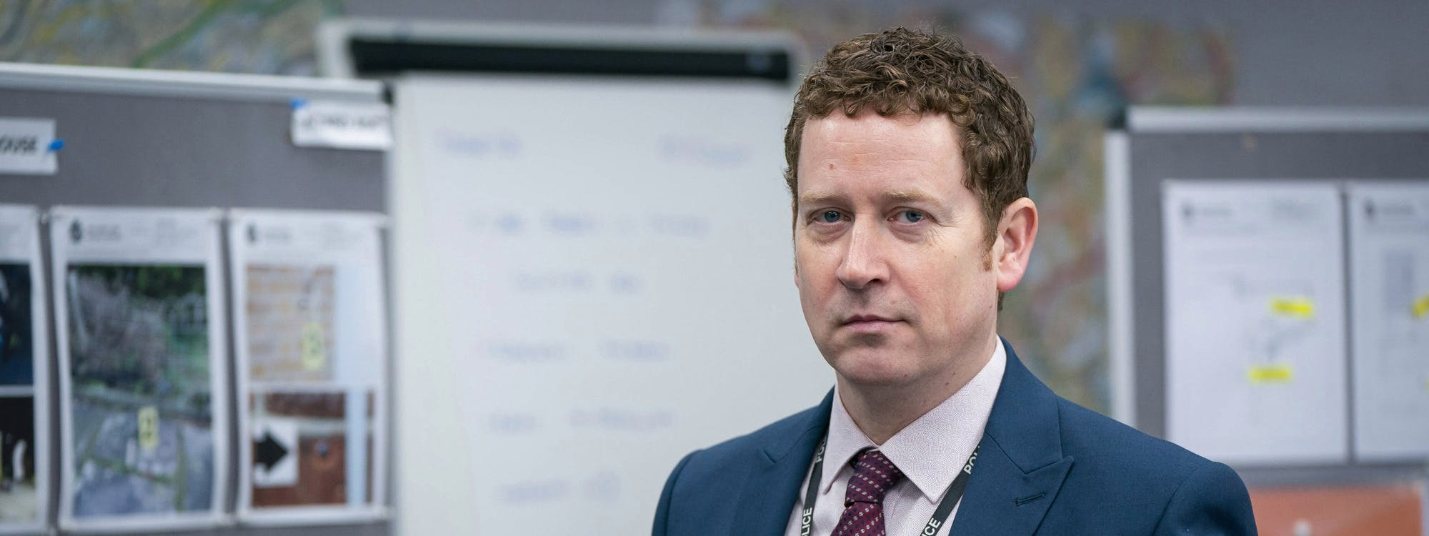 Image of Line of Duty actor Nigel Boyle in character as Ian Buckells, pictured from the chest up in the police station wearing a suit