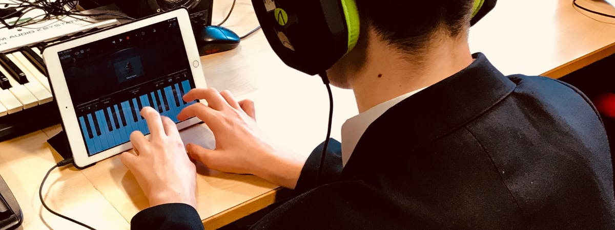 Picture of an Ipad and a student in headphone playing on a piano app