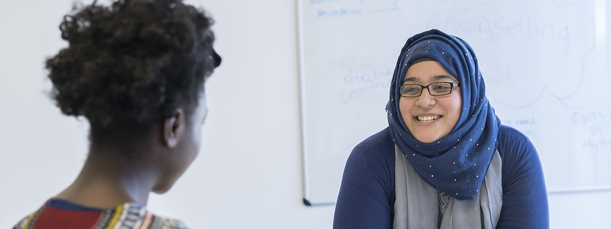Psychology with Business - BSc (Hons) Course Image 1200 x 450 - Two women speaking at a desk