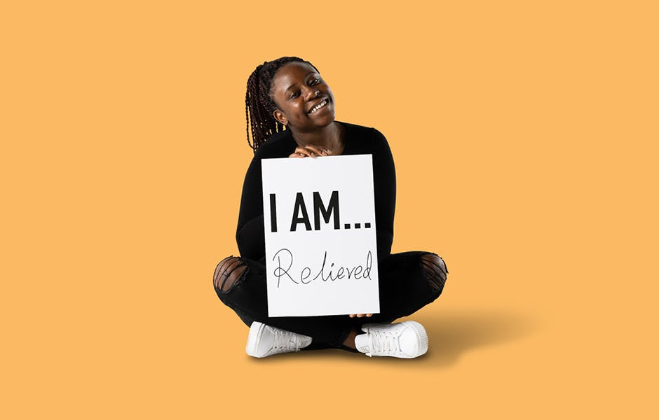 """学生Reine Chiriseri坐在地板上,手里拿着一块牌子,上面写着""""我松了一口气"""""""
