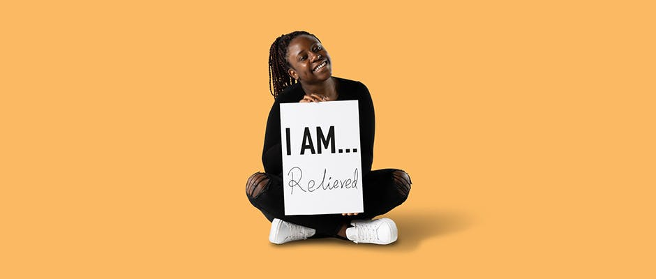 Student Reine Chiriseri sat on the floor holding a sign that says 'I AM Relieved'