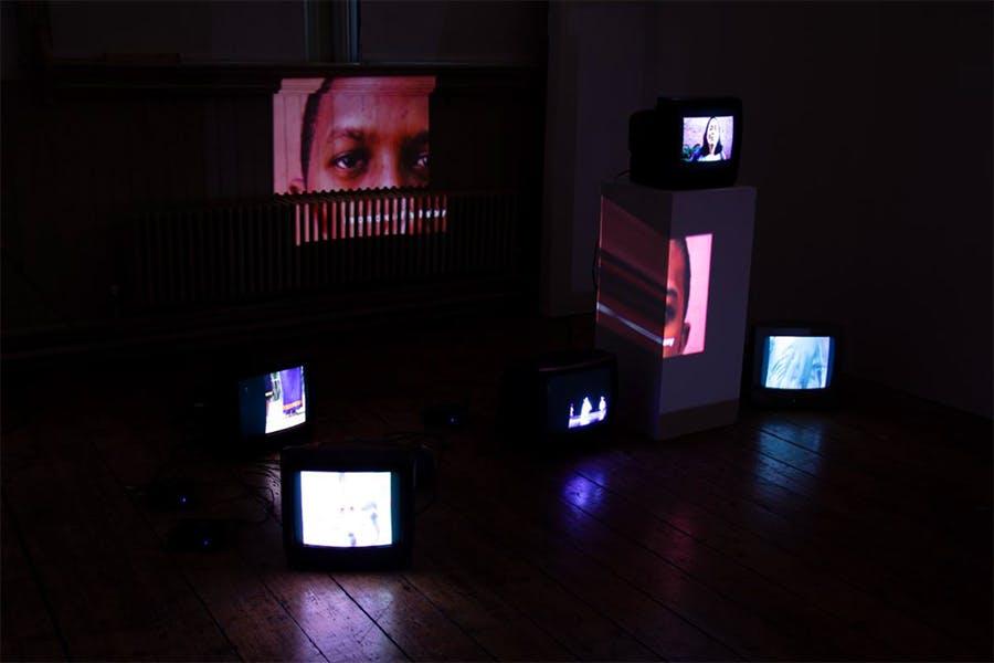 Fine Art installation: dark room with lots of old tv screens