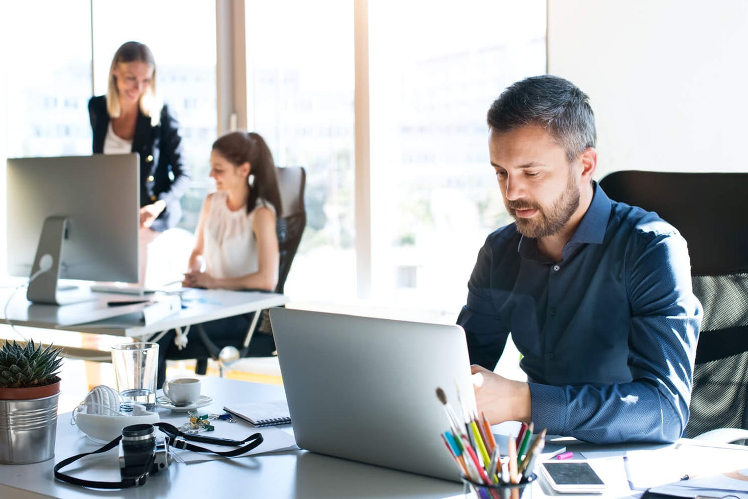 Man working at workstation with female coworkers talking in the background