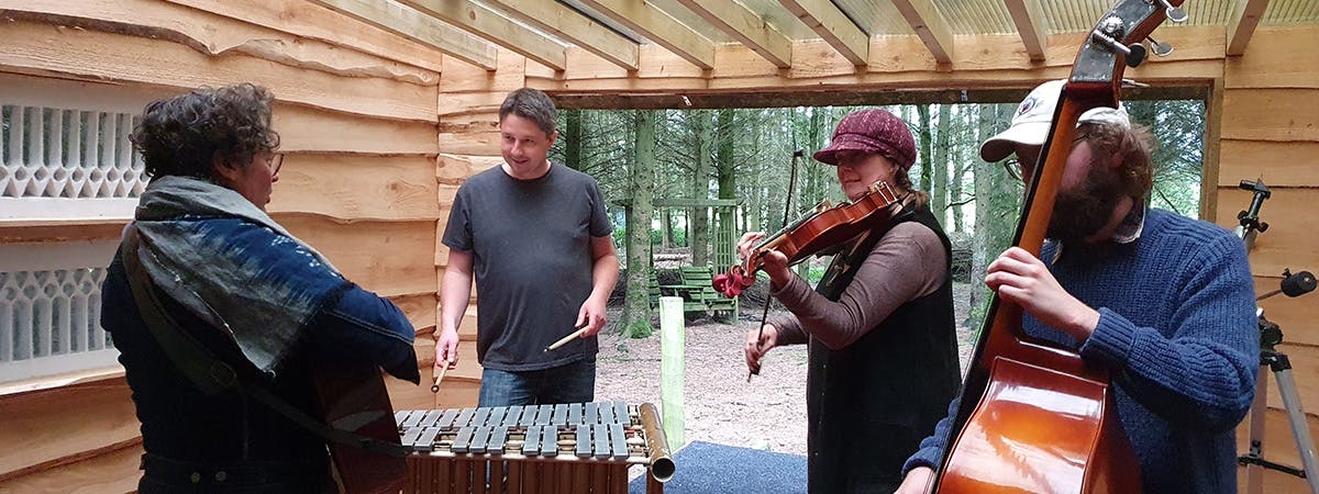 four-piece band in a forest setting
