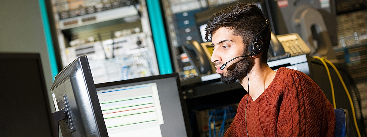 BCU CTN student wearing a headset at a computer.