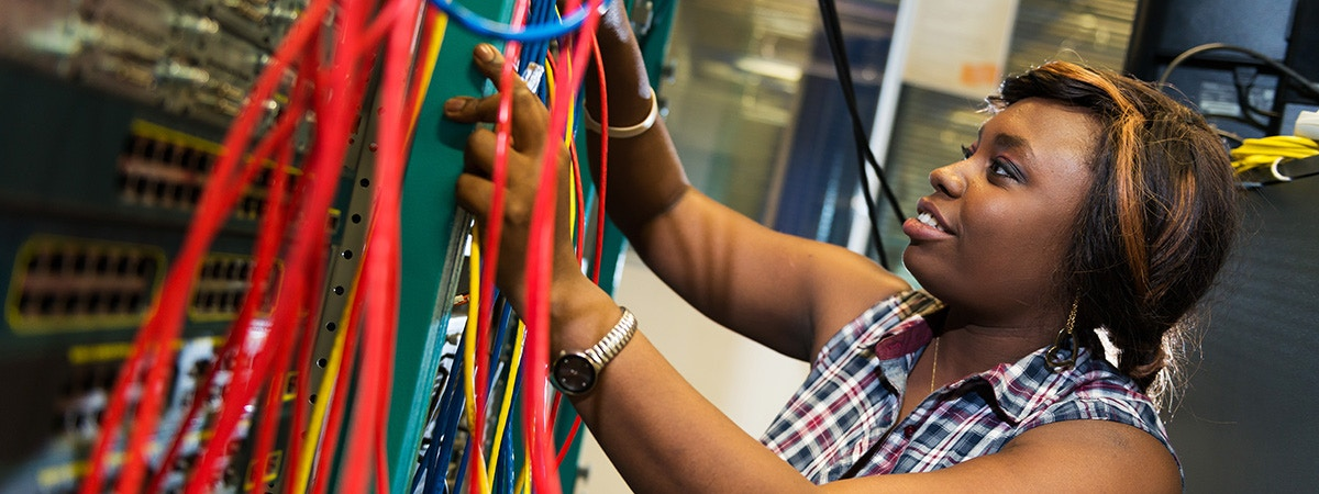 BCU CTN female student wiring up a computer network system.
