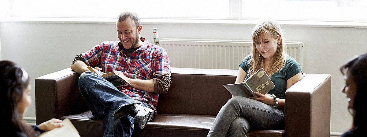 BCU English students on a sofa reading.