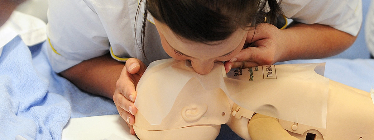 BCU Child Nursing student practicing mouth to mouth on a child dummy.