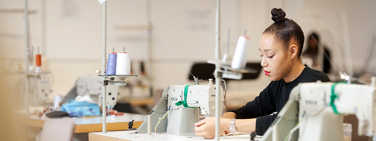 BCU Fashion & Textiles student operating a sewing machine.